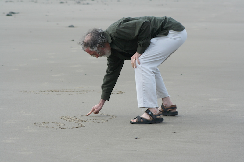 Paul Shaw draws letters on a sandy Oregon beach in 2011. Photo by Bronwen Job.