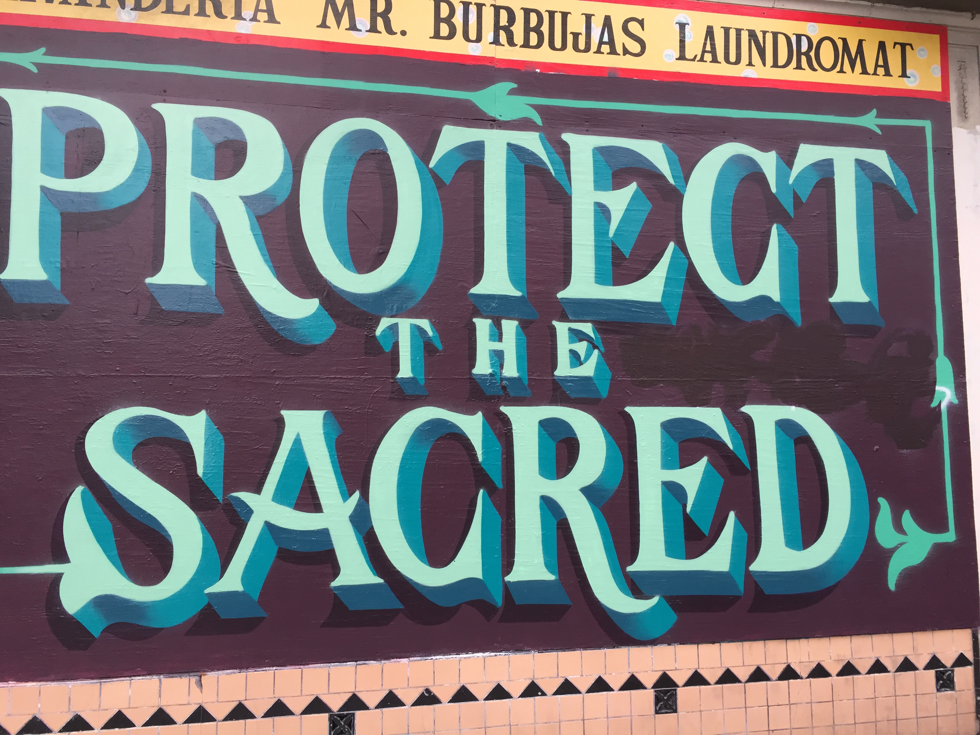 Protect the Sacred type mural with Mr. Burbujas sign painted above
